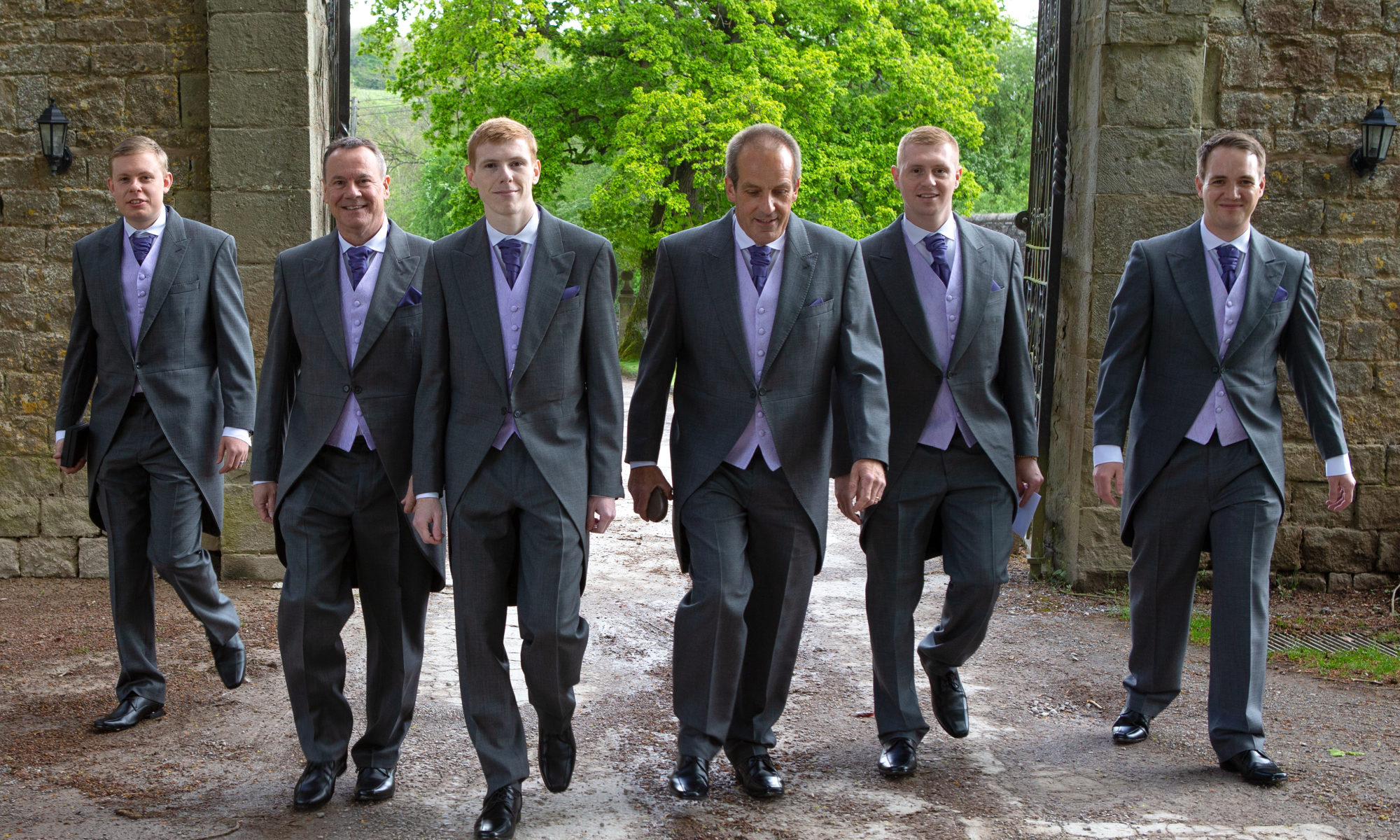 Groomsmen walking up the drive at Clearwell Castle